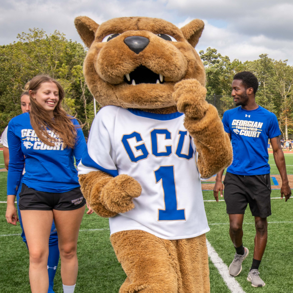 GCU mascot Roary the lion walking on a football field with three students